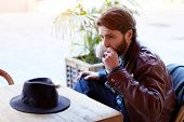 stock photo of coffee coffee plant  - Portrait of handsome fashionable hipster man drinking tea or coffee while sitting on the terrace of beautiful coffee shop flare sun light - JPG