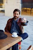 foto of coffee coffee plant  - Portrait of handsome hipster man paying for his coffee with a credit card at the cafe customer paying at a coffee shop with a credit card - JPG