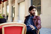 stock photo of coffee coffee plant  - Portrait of handsome and stylish man with beard enjoying a cup of coffee in a coffee shop adult fashionable hipster having coffee in beautiful cafe terrace - JPG