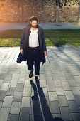 Постер, плакат: Portrait of a stylish young man with black hair and beard walking down the street on a sunny day