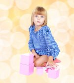 picture of montessori school  - Adorable little blonde girl is sitting on the floor and playing with blocks in Montessori kindergarten - JPG