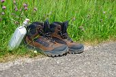 pic of canteen  - Hiking boots with a canteen stand on the wayside in front of a summer meadow - JPG