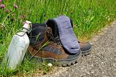 foto of canteen  - Hiking boots with socks and a canteen stand on the wayside in front of a summer meadow - JPG