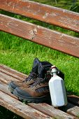 stock photo of canteen  - Hiking boots and a canteen on a seat bench in the nature - JPG