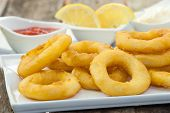 picture of deep  - deep fried calamari with lemon and salad on white tray - JPG