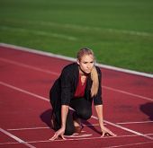 picture of race track  - business woman in start position ready to run and sprint on athletics racing track - JPG