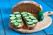 foto of cucumbers  - Freshly baked bread cucumber and sandwich with sliced cucumbers in rural or rustic kitchen on vintage wood table from above - JPG