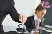picture of receptionist  - female receptionist worker ringing at hotel counter bell - JPG