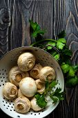image of champignons  - Fresh white champignons in a colander on dark wooden table - JPG