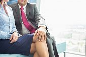 foto of office romance  - Midsection of businessman flirting with female colleague in office - JPG