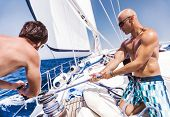 image of work crew  - Two handsome shirtless sailors working on sailboat - JPG