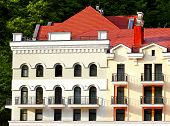 pic of red roof  - Facade of a massive building with a red roof and balconies - JPG