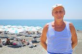 pic of vest  - Portrait of elderly man in a striped vest and a white cap on the beach near the sea - JPG