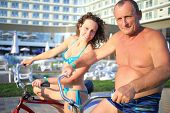 pic of bathing  - Portrait of elderly man and a young woman in bathing suits on bikes on the hotel in the evening - JPG