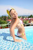 picture of bathing  - Portrait of a happy young girl in a bathing suit and swim cap in the pool - JPG
