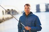 stock photo of street-rod  - Man in posing with the light rod near the river - JPG