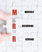 picture of revenue  - Hand of a business man completing the puzzle with the last missing piece - JPG