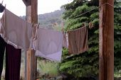 stock photo of rainy day  - Clothes drying outside on a clothesline on a rainy day - JPG