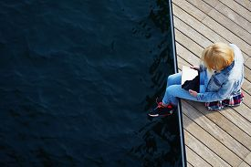 image of jetties  - Top view shot of a young blonde hair woman sitting on a jetty next to a sea while using busy digital tablet with a blank screen tourist woman searching information on tablet while relaxing on a pier - JPG