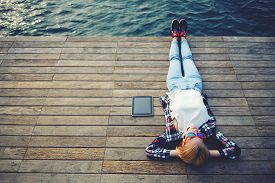 foto of jetties  - Top view young woman lying on a wooden jetty enjoying the sunshinetourist girl in bright glasses lying on jetty by river vintage photo of relaxing young woman in nature with tablet cross process