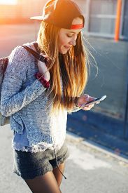 picture of cell  - Pretty girl walking outdoors in the street while using busy a smart phone gorgeous young woman wearing casual spring clothes walking down a city street while texting on her cell phone flare sun - JPG