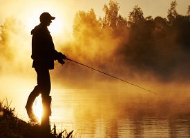 stock photo of rod  - Fisher man fishing with spinning rod on a river bank at misty foggy sunrise - JPG