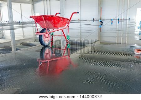 Wheelbarrow is at unfinished modern large showroom with reflection on the water surface.
