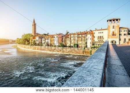 Verona cityscape view on the riverside with historical buildings and towers on the sunrise