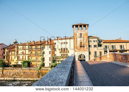 Verona cityscape view on the riverside with historical buildings and watchtower on the sunrise