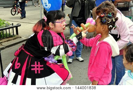 New York City - May 6 2012: A little girl interacts with Summer the Clown at a Broadway street festival