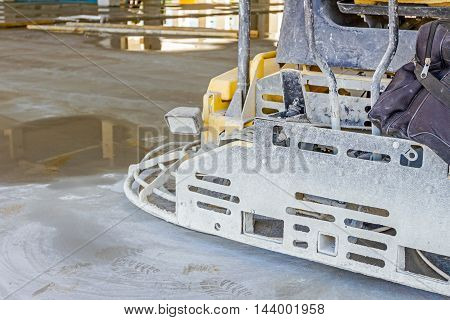 Detail of self leveling power trowel machine sander for smoothing surface on concrete slab.