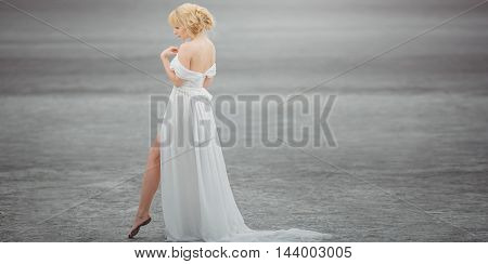 Bride outdoors in dried-up lake. Beautiful woman walking in white dress. Stretched wide landscape photo. Gray background with copy space.