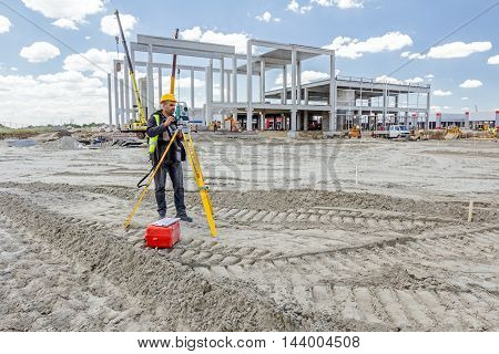 Zrenjanin Vojvodina Serbia - June 22 2015: Surveyor engineer is measuring level on construction site. Surveyors ensure precise measurements before undertaking large construction projects.