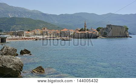 Budva Montenegro - June 22nd 2016. Tourists pack the beaches at the start of the holiday season in the Montenegrin coastal town of Budva. The old town stari grad can be seen on the right of the beach