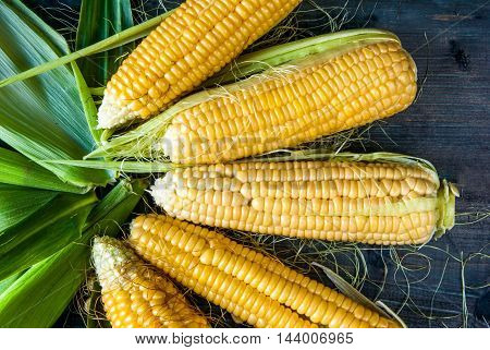 Fresh corn with leaves on a dark rustic wooden table, top view