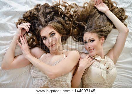 Female Portrait Of Cute Twins In Underwear Indoors. Close-up Beautiful Sexy Model Girls In Elegant P
