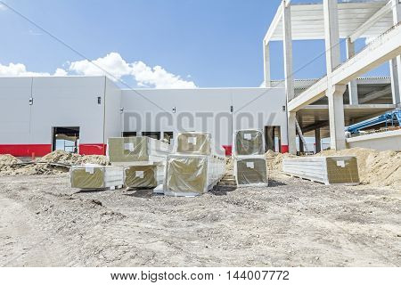 Wall insulation composite panels classified by the according to size and shape are wrapped in foil at construction site.