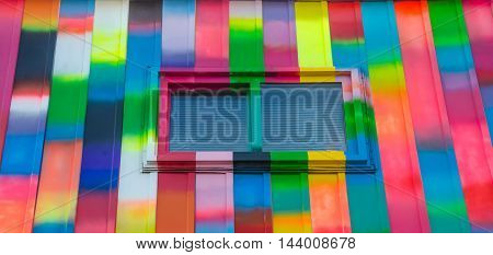 Abstract colour, bright, rectangular, rainbow coloured window and wall exterior.  Super colourfully bright painted aluminum panelled wall featuring small slider window with blind shades drawn.