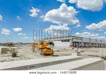 View on construction site with machinery people at work.