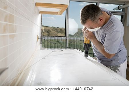 Manual worker drilling a hole on kitchen countertop.