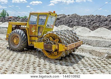 Construction worker is driving huge road roller with spikes and compacting soil for a large foundation.