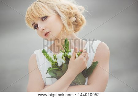 Portrait of a young beautiful bride loking at camera and gently embraces wedding bouquet outdoors on gray background. Professional make-up and hair-style.