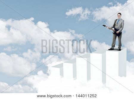 Full length of young businessman in suit standing on graph bars with guitar