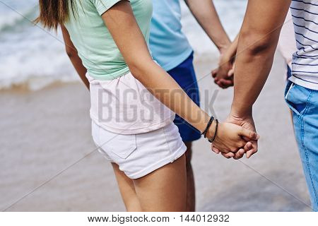 Cropped image of friends holding hands when standing on beach