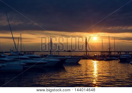 yacht standing at the pier at sunset in summer, in the distance, the cable-stayed bridge
