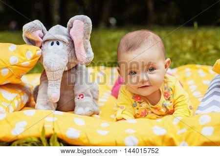 beautiful babe lying on a yellow curtain in a park with elephants