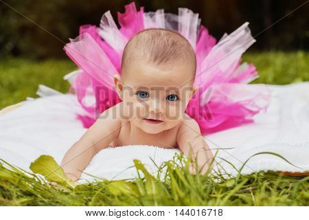 funny little an infant in a pink skirt lying on his stomach