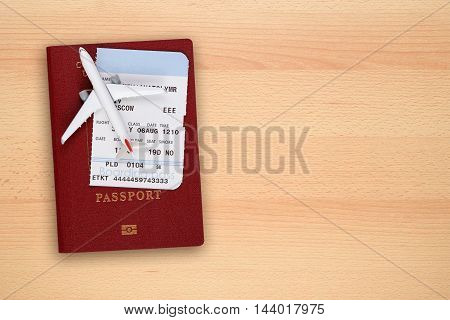 Boarding pass passport and toy aircraft on desk top view