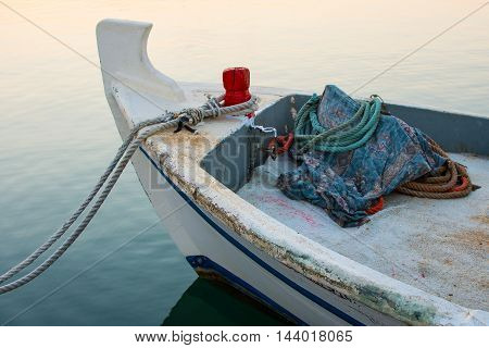 Old Fishing Boat Docked at Dawn. Small Wooden Boat on the Water Tide With Ropes. Sunrise in the Harbor and Calm Sea.