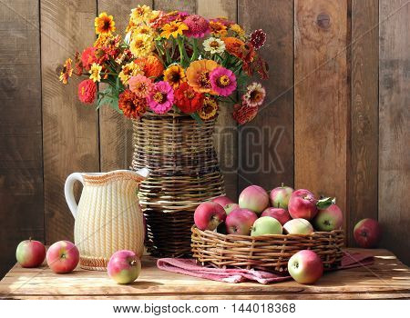 Still life with a bouquet of garden flowers jug and apples in the basket.